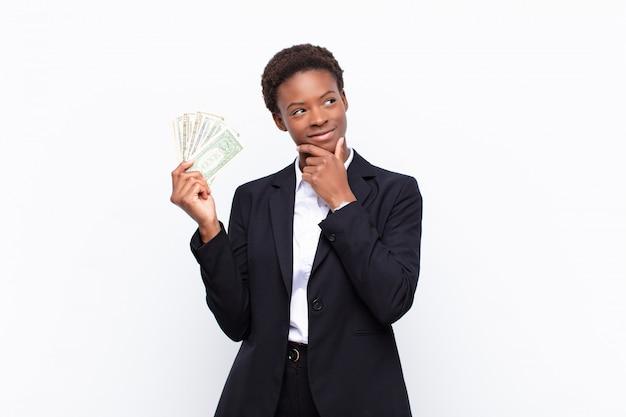 Młoda ładna czarna kobieta uśmiechająca się z radosnym, pewnym siebie wyrazem twarzy z ręką na brodzie, zastanawiająca się i spoglądająca w bok z banknotami dolarowymi