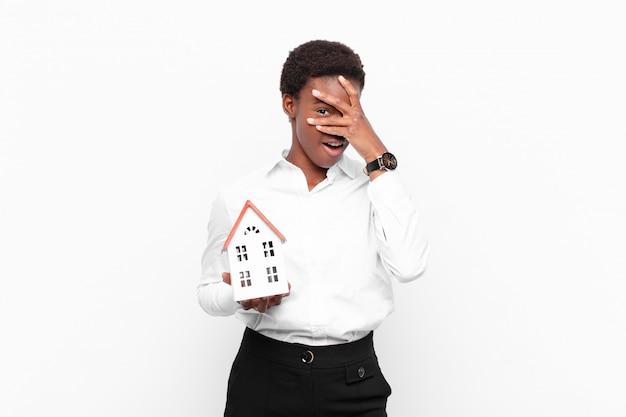 Młoda, ładna, czarna kobieta wygląda zszokowana, przestraszona lub przerażona, zakrywa twarz dłonią i zagląda między palcami model domu