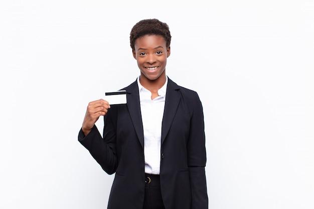 Młoda, ładna, czarna kobieta wyglądająca na szczęśliwą i mile zaskoczoną, podekscytowaną zafascynowanym i zszokowanym wyrazem twarzy z kartą kredytową
