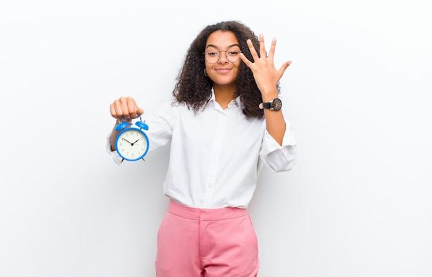 Młoda ładna czarna kobieta z budzikiem na białej ścianie