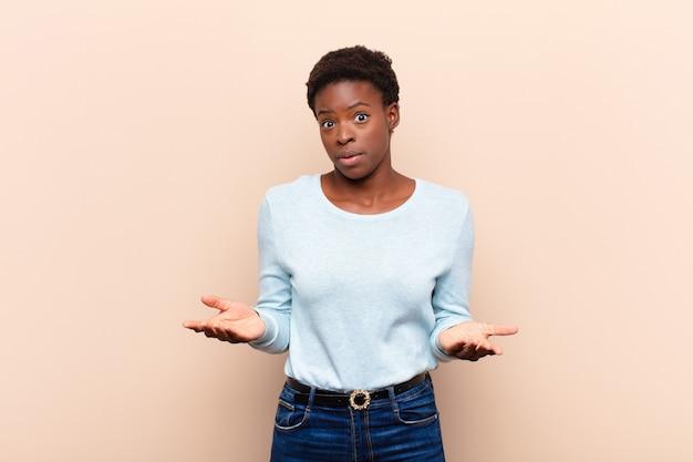 Młoda ładna czarna kobieta z otwartymi ustami i zdumiona, zszokowana i zdziwiona niewiarygodną niespodzianką