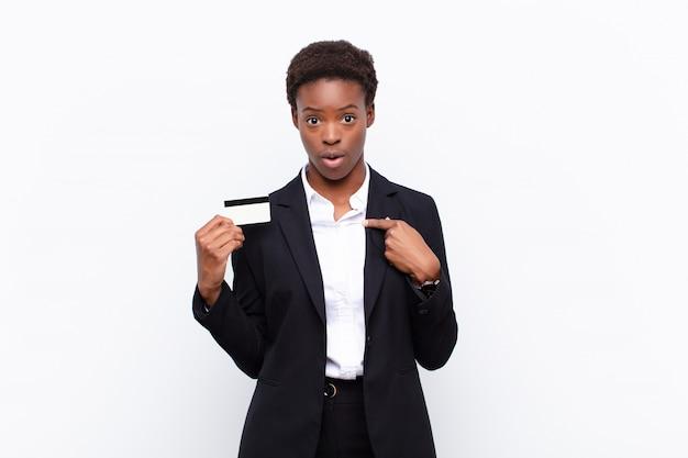 Młoda ładna Czarna Kobieta Zszokowana I Zaskoczona Szeroko Otwartymi Ustami, Wskazująca Na Siebie Z Kartą Kredytową Premium Zdjęcia