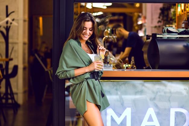 Młoda ładna dama korzystająca z wolnego czasu w miejskiej kawiarni i barze, pijąc cytrynę i bawiąc się, modny strój hipster, stonowane kolory.