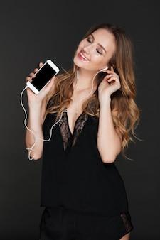Młoda ładna dama trzyma telefon i słuchania muzyki