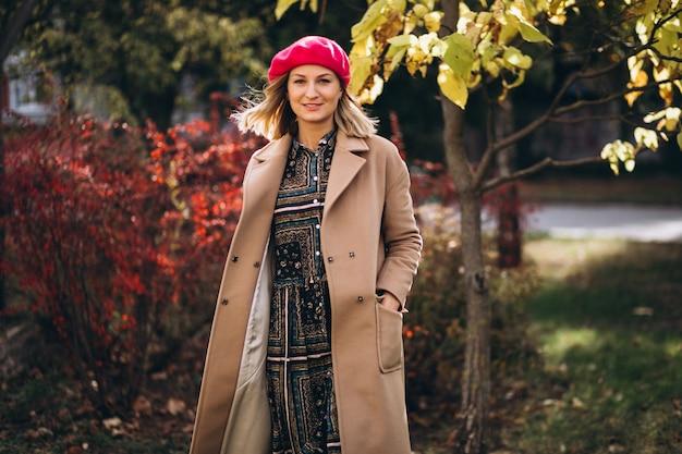 Młoda ładna dama w czerwonej barret na zewnątrz w parku
