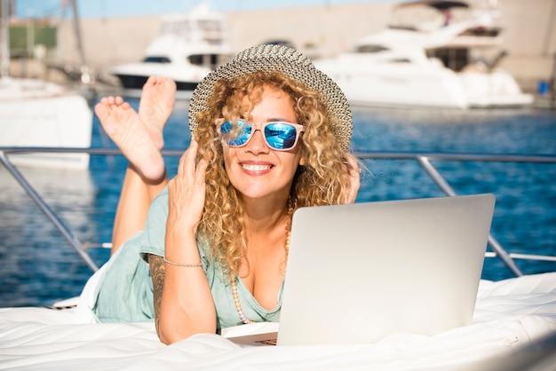 Młoda ładna dorosła kobieta uśmiechać się i używać komputera przenośnego na zewnątrz położyć się na pokładzie jachtu