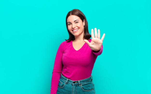 Młoda ładna dorywcza kobieta uśmiecha się i wygląda przyjaźnie, pokazując numer pięć lub piąty z ręką do przodu, odliczając