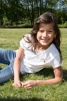 Młoda ładna dziesięć dziewczyna kłama na zielonej trawie
