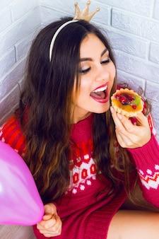 Młoda ładna dziewczyna bawi się na przyjęciu urodzinowym, ubrana w sweter z koroną imprezową, trzyma różowy balon i smaczny mały tort owocowy. pozytywne emocje, czytane do świętowania.