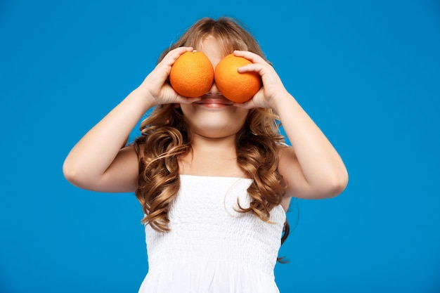 Młoda ładna dziewczyna chuje oczy dowcip pomarańcze nad błękit ścianą