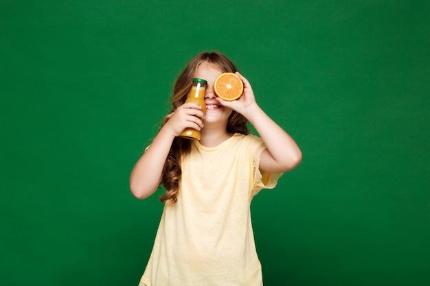 Młoda ładna dziewczyna chuje oczy z pomarańczami nad zieleni ścianą