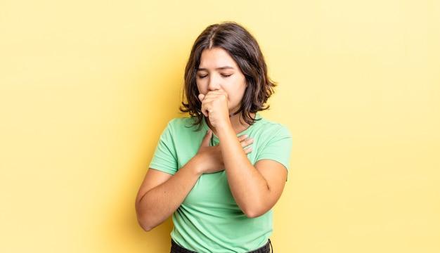 Młoda ładna dziewczyna czuje się chora z bólem gardła i objawami grypy, kaszle z zakrytymi ustami