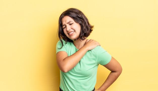 Młoda ładna dziewczyna czuje się zmęczona, zestresowana, niespokojna, sfrustrowana i przygnębiona, cierpi z powodu bólu pleców lub karku