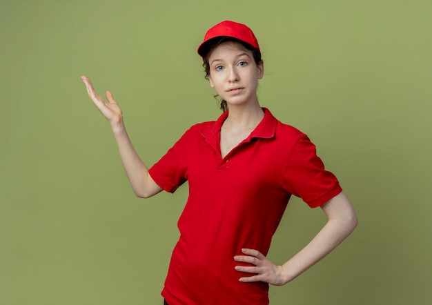 Młoda ładna dziewczyna dostawy w czerwonym mundurze i czapce, patrząc na kamery, kładąc rękę na talii i pokazując pustą dłoń odizolowaną na oliwkowym tle z miejsca na kopię