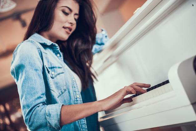 Młoda ładna dziewczyna gra na pianinie w sklepie muzycznym