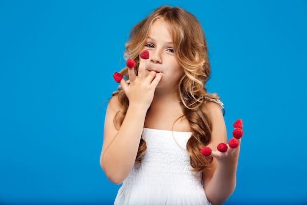 Młoda ładna dziewczyna je malinki na niebieską ścianą