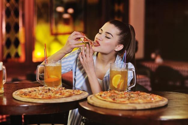 Młoda ładna dziewczyna jedząca pizzę i pijąca piwo lub piwny koktajl z cytrusów na powierzchni baru lub pizzerii.