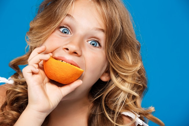 Młoda ładna dziewczyna jedzenie pomarańczy na niebieską ścianą