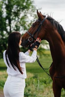 Młoda ładna dziewczyna jeźdźca pozuje na ranczo w pobliżu pełnej krwi ogiera. jazda konna, wyścigi konne.