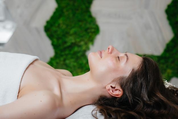 Młoda ładna dziewczyna korzysta z profesjonalnego masażu głowy w spa. pielęgnacja ciała. salon piękności.