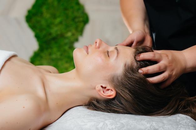 Młoda ładna dziewczyna korzysta z profesjonalnego masażu głowy w spa