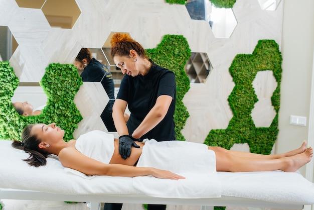 Młoda ładna dziewczyna korzysta z profesjonalnego masażu kosmetycznego w spa