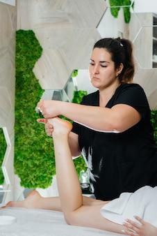 Młoda ładna dziewczyna korzysta z profesjonalnego masażu miodem w spa. pielęgnacja ciała. salon piękności.
