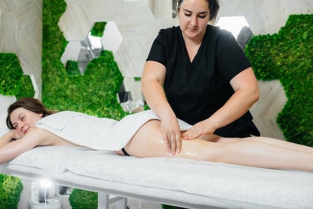 Młoda ładna dziewczyna korzysta z profesjonalnego masażu miodem w spa