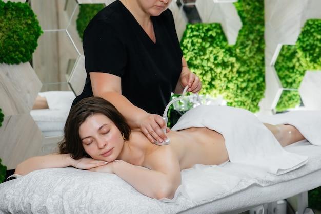 Młoda ładna dziewczyna korzysta z profesjonalnego masażu podciśnieniowego w spa. pielęgnacja ciała. salon piękności.