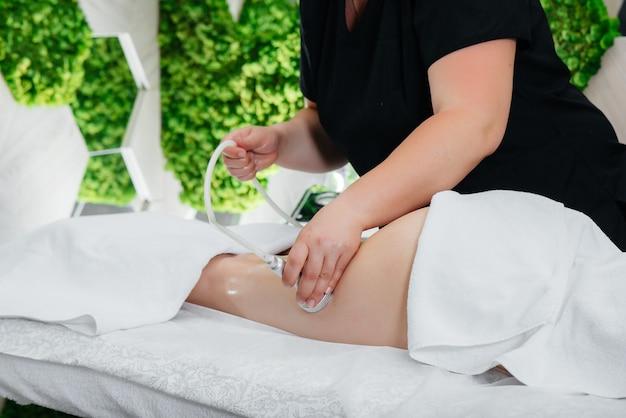 Młoda ładna dziewczyna korzysta z profesjonalnego masażu podciśnieniowego w spa