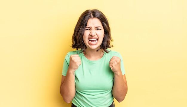 Młoda ładna dziewczyna krzyczy agresywnie ze zirytowanym, sfrustrowanym, gniewnym spojrzeniem i zaciśniętymi pięściami, czując się wściekły