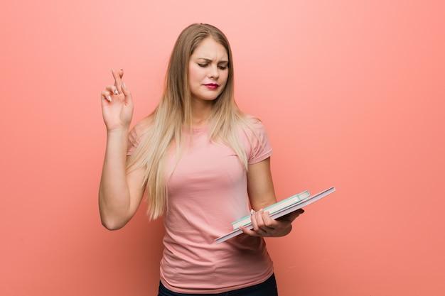 Młoda ładna dziewczyna krzyżuje palce za mieć szczęście. ona trzyma książki.