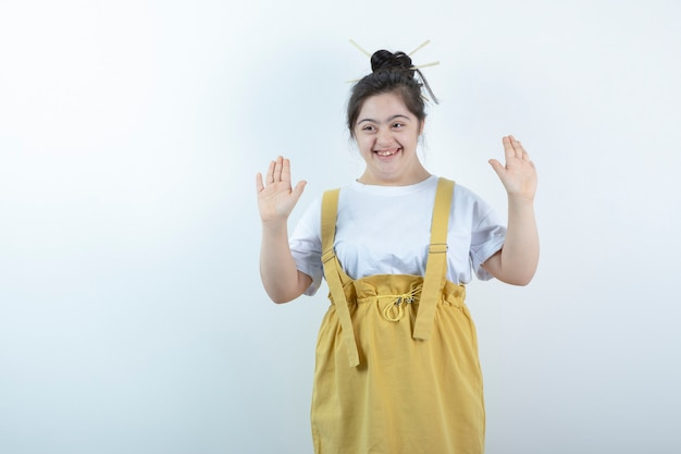 Młoda ładna dziewczyna model stojąc i pozowanie przed białą ścianą.