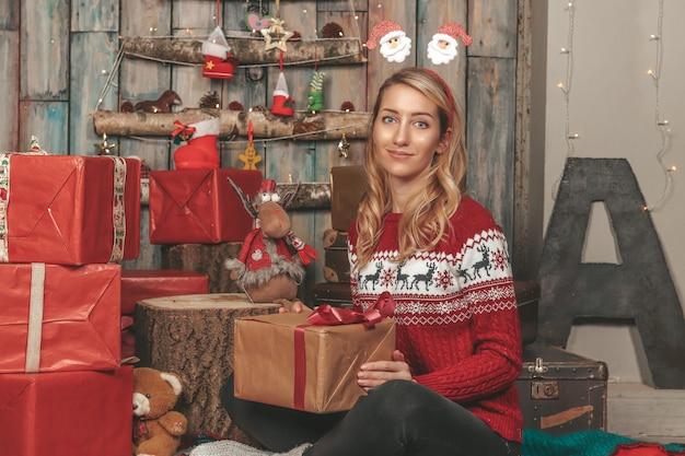 Młoda ładna dziewczyna na obrazie sylwestrowym wśród prezentów i dekoracji świątecznych