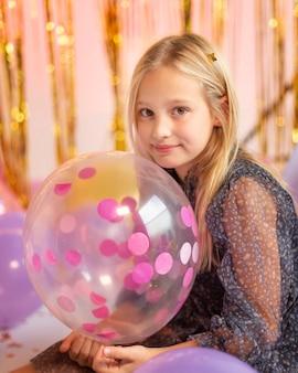 Młoda ładna dziewczyna na uroczystej imprezie z balonami