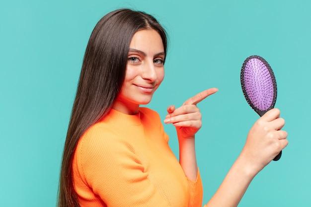 Młoda ładna dziewczyna nastolatek. wskazujący gest. koncepcja szczotki do włosów