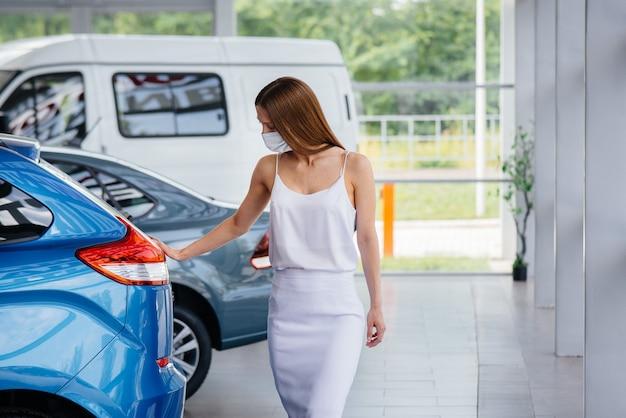 Młoda ładna dziewczyna ogląda nowy samochód w salonie samochodowym w masce podczas pandemii. sprzedaż i kupno samochodów w okresie pandemii.
