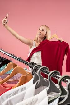 Młoda ładna dziewczyna patrząc na sukienki i przymierzając ją wybierając w sklepie