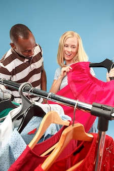 Młoda ładna dziewczyna patrzy na sukienki i przymierza je, wybierając w sklepie