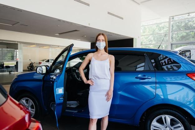 Młoda ładna dziewczyna podczas pandemii ogląda nowy samochód w salonie samochodowym w masce. sprzedaż i kupno samochodów w okresie pandemii.