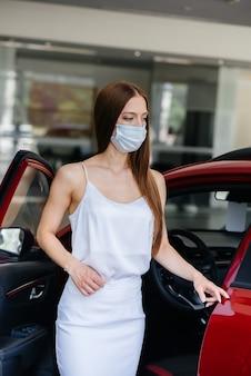 Młoda ładna dziewczyna podczas pandemii ogląda nowy samochód w salonie samochodowym w masce. sprzedaż i zakup samochodów w okresie pandemii.