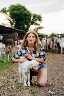 Młoda ładna dziewczyna pozuje na ranczo z kozami i innymi zwierzętami
