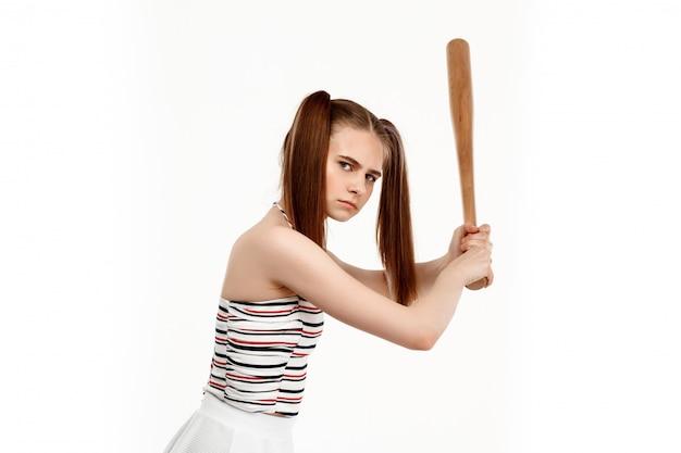 Młoda ładna dziewczyna pozuje z nietoperzem, odosobnionym na biel ścianie