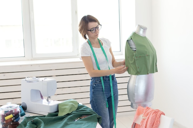 Młoda ładna dziewczyna projektantka krawcowa z okularami i miarką tworzy nowy produkt za pomocą zielonego sukna i krawieckiego manekina. koncepcja warsztatu krawieckiego.