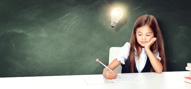 Młoda ładna dziewczyna przy tablicy z żarówką nad głową