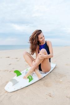 Młoda ładna dziewczyna relaksuje się na plaży, siedząc na swojej desce surfingowej