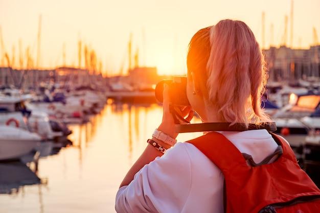 Młoda ładna dziewczyna robi zdjęcie zatoki z jachtami o zachodzie słońca
