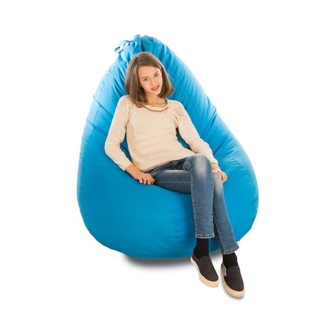Młoda ładna dziewczyna siedzi na niebieski worek fasoli na białym tle