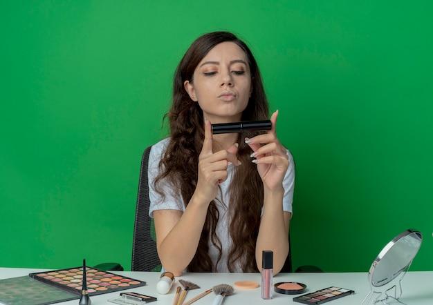 Młoda ładna dziewczyna siedzi przy stole do makijażu z narzędzi do makijażu, trzymając i patrząc na tusz do rzęs na białym tle na zielonym tle