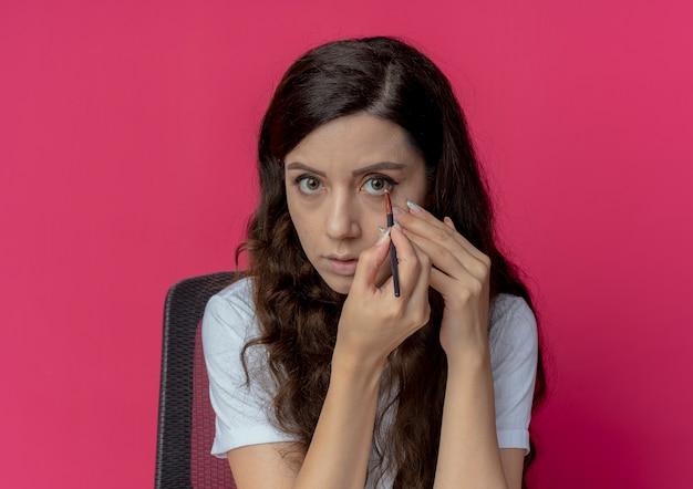 Młoda ładna dziewczyna siedzi przy stole do makijażu z narzędziami do makijażu, dotykając twarzy i nakładając cień do powiek pędzlem do makijażu, patrząc na aparat odizolowany na szkarłatnym tle